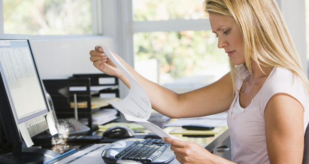 Woman in home office with computer and paperwork frowning