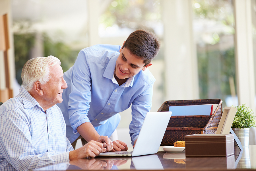 Funeral Insurance Teenage Grandson Helping Grandfather With Laptop