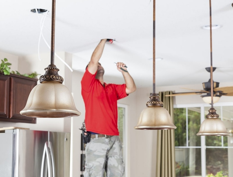 Man installing ceiling pendant lights and recessed lighting in kitchen